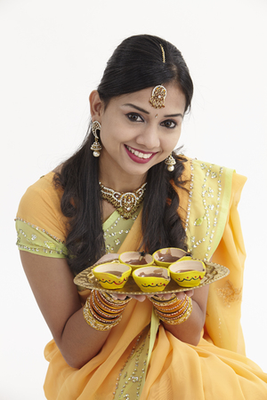 Foto de Indian woman in glamorous traditional clothing holding oil lamp - Imagen libre de derechos