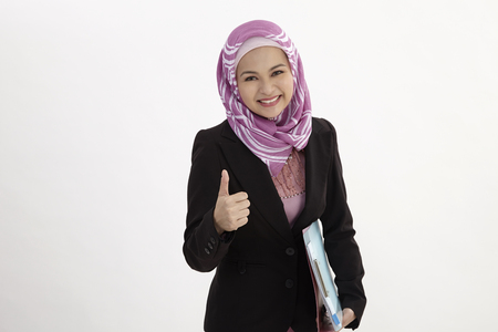Photo for malay woman wearing  business suit holding document files with thumb's up - Royalty Free Image