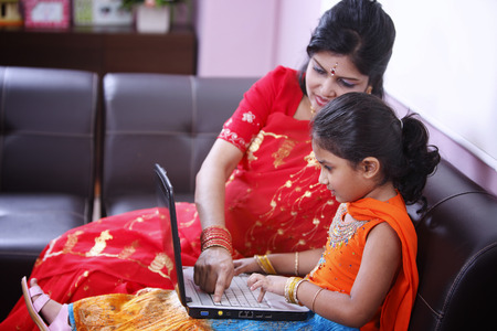 Photo for Mother teaching daughter using laptop - Royalty Free Image