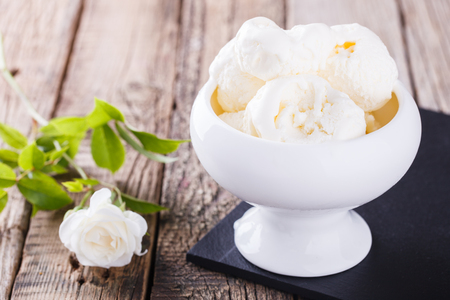 Photo for Ice cream, white cream in a white ceramic bowl with white roses.selective focus - Royalty Free Image