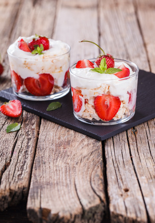 Photo for Eton Mess - Strawberries with whipped cream and meringue in a glass beaker. Classic British summer dessert.selective focus - Royalty Free Image