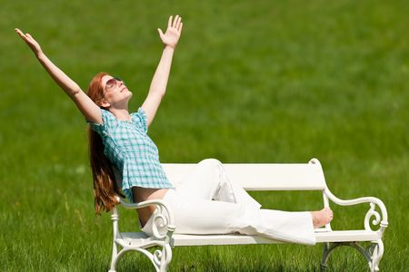 Red hair woman enjoying sun on white bench in a meadow; shallow DOF