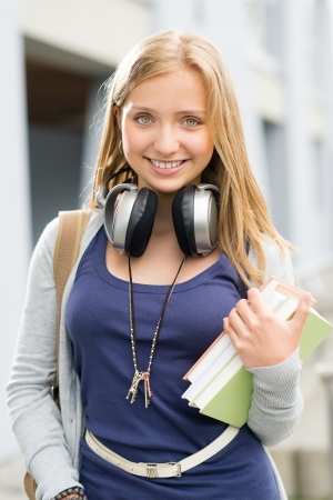 Young teenage student girl with books headphones smiling at camera