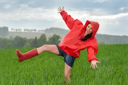 Photo pour Playful teenage girl dancing in the rain on a field - image libre de droit