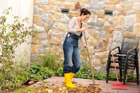 Photo pour Young woman sweeping autumn leaves veranda backyard cleaning pile - image libre de droit