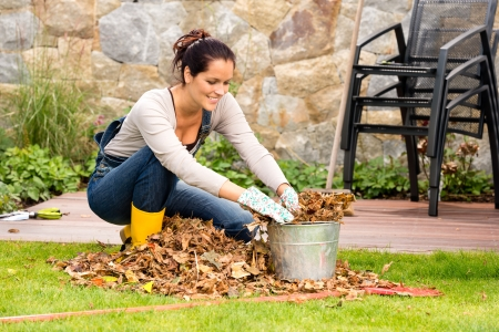 Photo for Smiling woman stuffing dry leaves into bucket autumn garden housework - Royalty Free Image