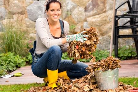 Foto de Smiling woman putting leaves in bucket fall garden housework - Imagen libre de derechos