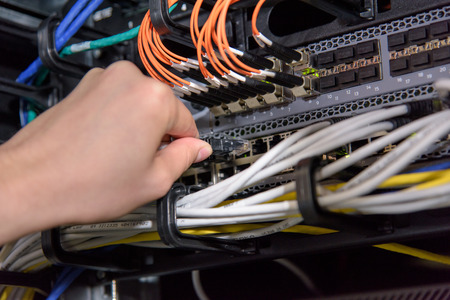 Photo pour Hand connecting network cable to server patch panel in datacenter - image libre de droit