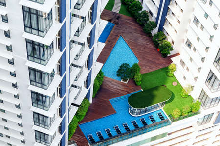 Photo pour Details of modern building exterior - patio in high-rise building with swimimg pool, lounge zone, green trees. Everything for comfortable stay, ideal exotic vacation. - image libre de droit