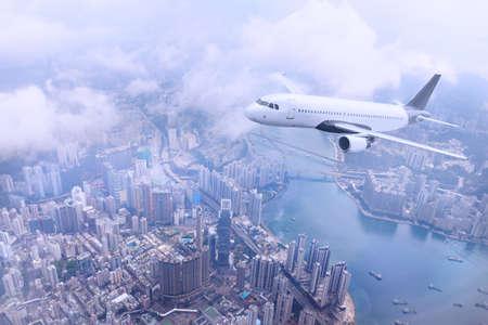 Foto de Passenger plane fly to Hong Kong Island. Aerial view at cityscape. Airplane over urban skyline. Concept of travel and air transportation. - Imagen libre de derechos