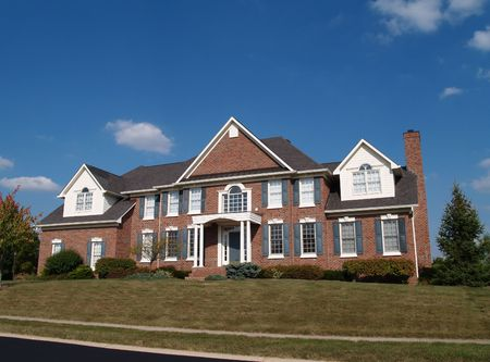 Large two story brick residential home with blue shutters and dormers.
