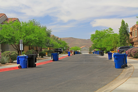 Photo for Blue trash cans line the street on trash day in a Tucson Neighborhood with blue sky copy space. - Royalty Free Image