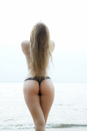 sexy girl with a figure standing at the sea showing her ass