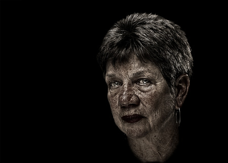 Portrait of a senior elderly older woman lady with short hair and desaturated with exaggerated flaws wisdom marks inlcuding wrinkles sunspots with serious judging melancholy sad depressed serious expression isolated on black background