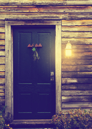 Old rustic vintage antique house home building structure with green intricate front door and window with shutters closed and porch light on