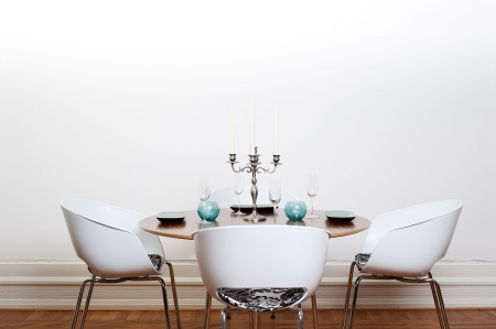 Modern dining room with a round table and  white chairs and background.