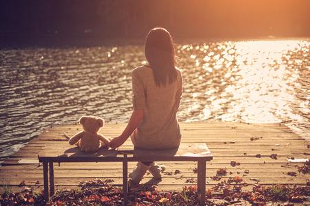 Foto de Woman and teddy bear sitting bench - Imagen libre de derechos