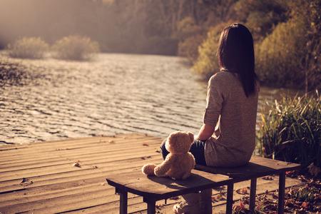 Photo pour Woman and teddy bear sitting bench - image libre de droit