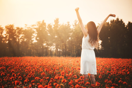 Photo for Young girl on poppy field hands up - Royalty Free Image