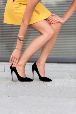 Close-up portrait of slim and slender woman's legs on high heels. Fashion lady in little yellow dress walking in the city centre.