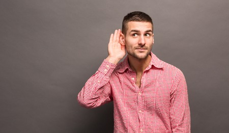 Foto de Listening male holds his hand near his ear over grey background. Handsome man trying to listen to the conversation of someone. - Imagen libre de derechos