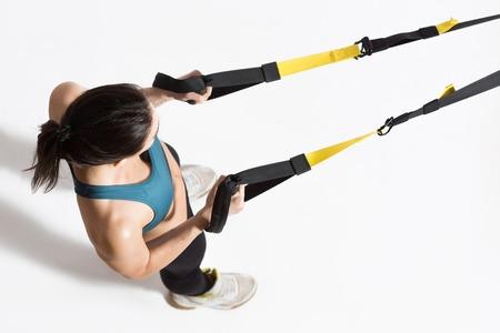 Foto de Top view of pretty young lady training upper body on suspension trainer sling. - Imagen libre de derechos