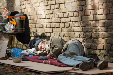 Foto de Sleeping homeless man lying on cardboard. - Imagen libre de derechos