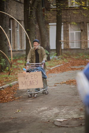 Photo pour Hopeless old tramp with cart and board with sign need money. - image libre de droit