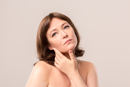 Foto de Nice woman with thoughtful face touching her cheeck. Isolated on white background. Mid age woman over 35 years old concept. - Imagen libre de derechos