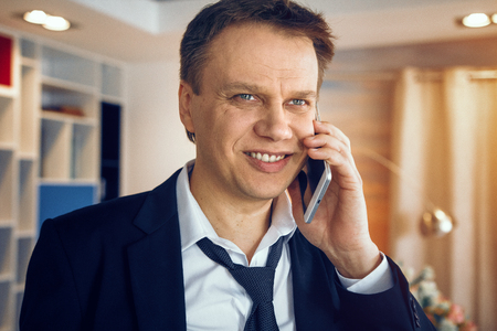 Photo for Handsome businessman working from home. Standing middle room and speaking over phone. - Royalty Free Image