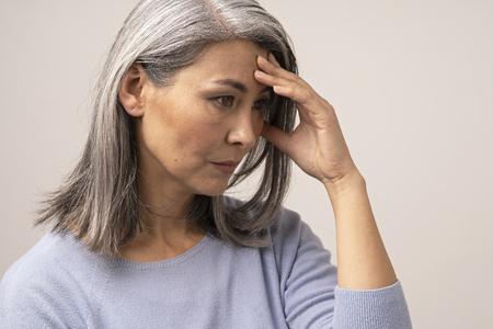 Photo pour Upset Asian Woman Is Touching Her Forehead. Side View Of Tired Middle-Aged Woman Almost Crying And Covering Her Face With A Hand. Portrait. - image libre de droit