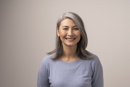 Photo pour Charming Middle-Aged Asian Woman Broadly Smiles At Camera. Horizontal Studio Shot Of Graceful Smiling Woman. Portrait - image libre de droit