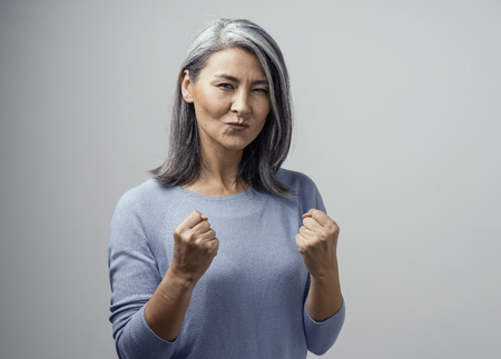 Foto de Happy Mature Asian Female Model Smiles Happily. She Celebrates Victory and Holds Fists in Satisfaction. Hand Photo in Studio on White Background - Imagen libre de derechos