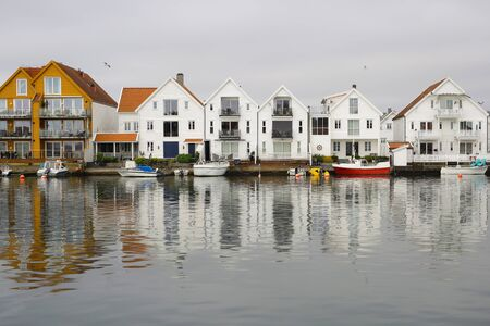 Foto de Marina in the Norwegian town Skudeneshavn. Old Skudeneshavn is one of the most well kept old towns of Europe and a quiet harbour for tall ships and small boats alike. Narrow streets, the idyllic harbour and the old white wooden houses in Skudeneshavn. - Imagen libre de derechos