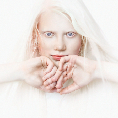 Photo pour Albino girl with white skin, natural lips and white hair. Photo face on a light background. Portrait of the head. Blonde girl - image libre de droit
