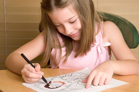 A young girl coloring in a Christian coloring book