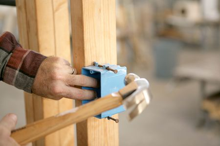 A closup of an electrician\'s hands installing an electrical box. Room for text.