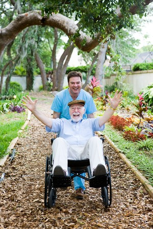 Caring nursing home orderly pops a wheelie with an elderly man's wheelchair.  They are having fun.