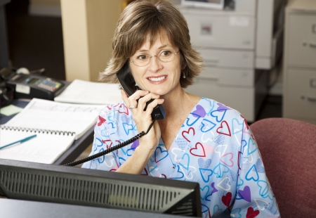 Busy medical receptionist working the front desk at a doctor's office.