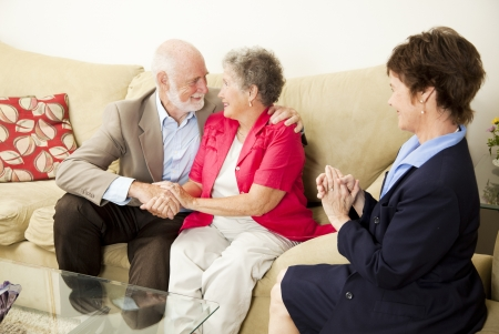 Therapist looks on as a senior couple she\'s been counseling works out their issues.