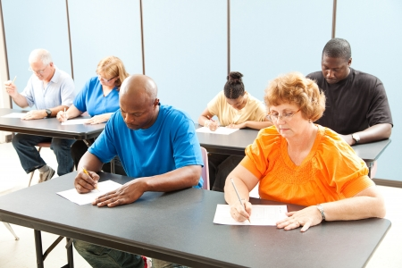 Photo for Diverse adult education class taking a test in the classroom.   - Royalty Free Image