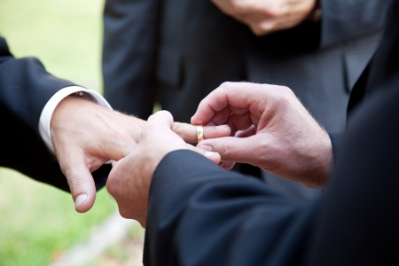 One groom placing the ring on another man's finger during gay wedding.