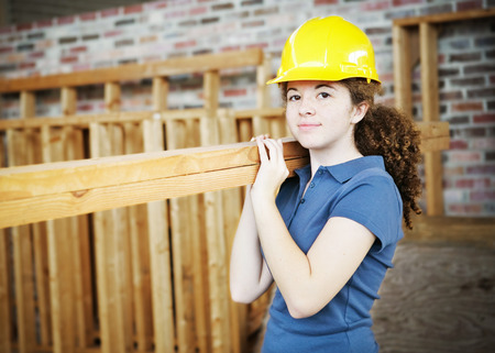 Photo for Young female apprentice carrying boards on a construction site.   - Royalty Free Image