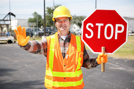 Foto de Friendly construction worker in the road holding up a stop sign. - Imagen libre de derechos