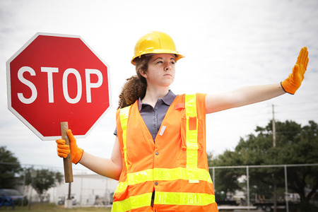 Photo pour Female construction apprentice holding a stop sign and directing traffic. - image libre de droit