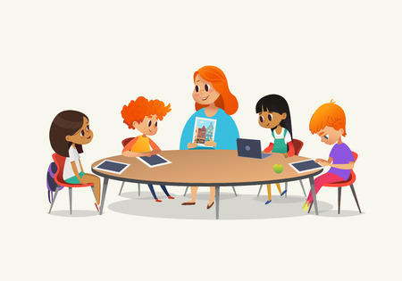 Illustration pour Redhead female teacher showing picture to children sitting around round table at class with laptop and tablet pc. Kids using gadgets during lesson at primary school. Colorful vector illustration - image libre de droit
