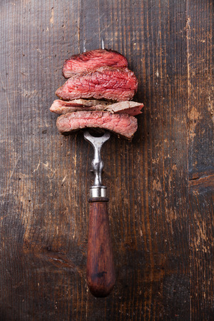 Photo for Slices of beef steak on meat fork on wooden background - Royalty Free Image
