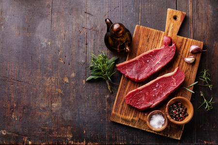 Raw fresh meat Striploin steak and seasoning on dark wooden background