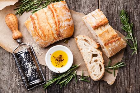 Foto de Sliced bread Ciabatta and extra virgin Olive oil on wooden background - Imagen libre de derechos