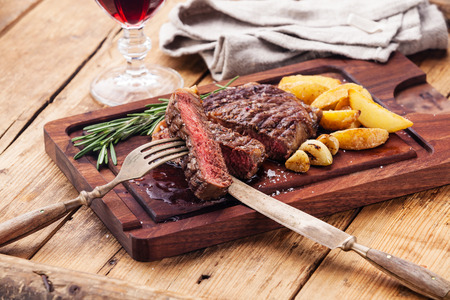 Photo for Medium rare grilled Beef steak Ribeye with roasted potato wedges on cutting board on dark wooden background - Royalty Free Image